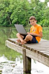 Freundlicher Junge sitzt mit Notebook auf dem Schoß am  Teich
