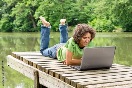 Frau mit Notebook am idyllischen Teich - Home Office