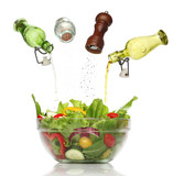 Pouring condiments on a colorful salad. isolated