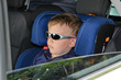 Serious little boy in car