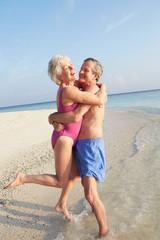 Senior Couple Having Fun On Tropical Beach Holiday