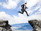 businessman jumping over danger precipice