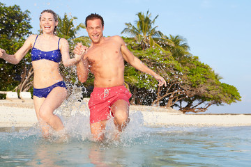 Couple Splashing In Sea On Tropical Beach Holiday