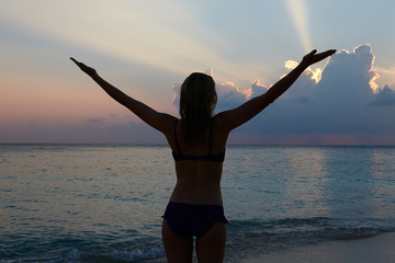 Silhouette Of Woman With Outstretched Arms On Beach