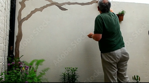man painting vine on wall
