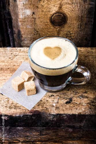 Small cup of espresso coffee in glass with heart drawning on fo
