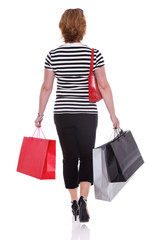 Rear view of a woman carrying shopping bags isolated.