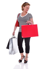 Female shopper with shopping bags checking her watch isolated.