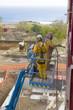 Ouvriers effectuant le sablage d'une structure industrielle