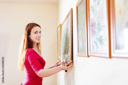 Positive  girl hanging  pictures