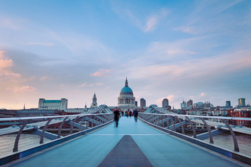 People walking over Millennium bridge at dusk.