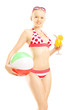 Young female in bikini holding a beach ball and cocktail