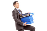 Young businessman carrying heavy folders