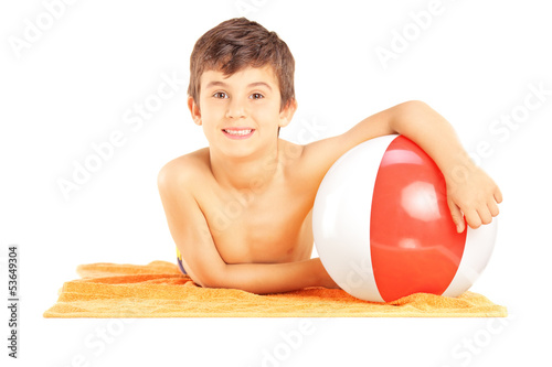 Smiling kid lying on a beach towel and holding a ball