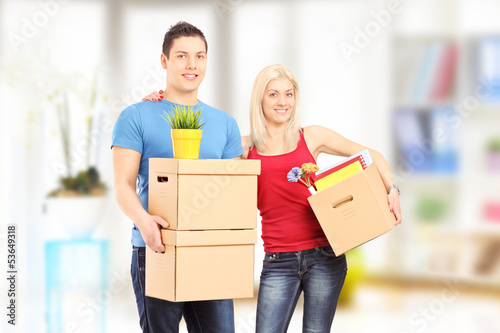 Young couple holding boxes and posing at new home