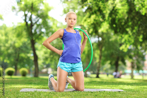 Young female athlete on a mat holding a hula hoop in a park