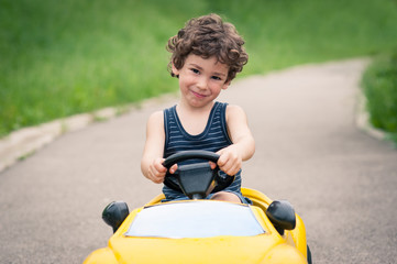 Young kid close up portrait with toy car outdoors.