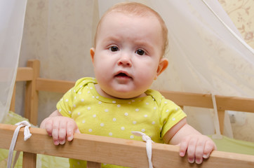 Surprised baby in a cot