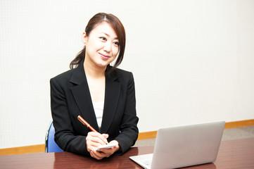 パソコン作業とメモを書く女性社員