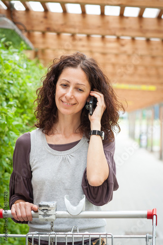 Smiling woman talking at the phone while holding a shopping cart