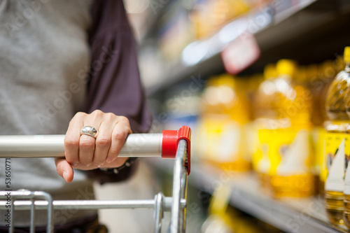 Woman hand close up with shopping cart in a supermarket walking