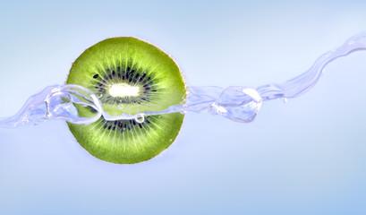 Water jet around kiwi on blue background