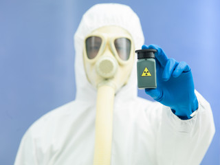 person in protective suit holding isotope sample