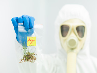 person in protective suit presenting crop sample