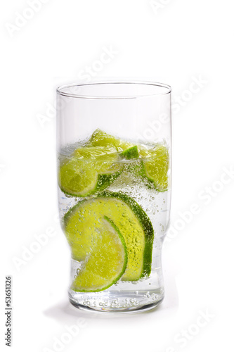 Glass of soda water with cut limes