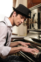 Virtuoso playing piano. Side view of handsome young men playing