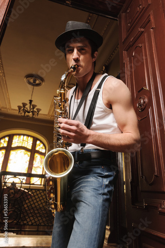 Virtuosic play. Low angle view of handsome men playing saxophone