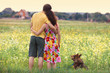 Young couple hugging in the field and looking at the village