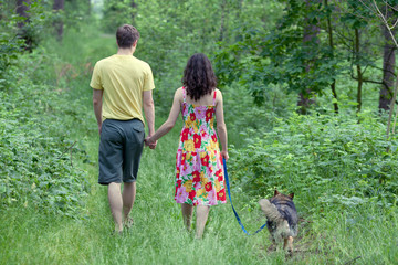 Young couple holding hands and walking with dog in the forest