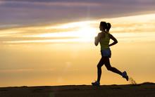 Sportler laufen bei Sonnenuntergang am Strand