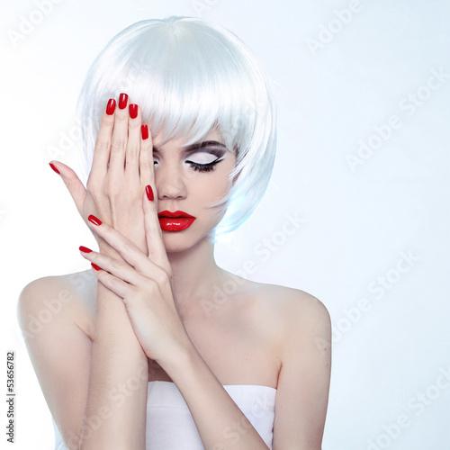 Beauty Woman portrait with makeup and red nail polish, studio sh