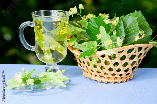 Cup of linden tea and basket with flowers