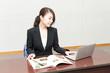 資料とパソコンで調べ物をする女性社員