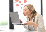 woman with computer kissing the screen