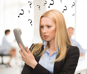 confused woman with phone in office