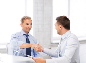 businessmen shaking hands in office