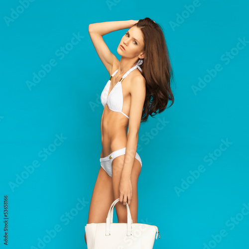 model posing in white bikini with handbag