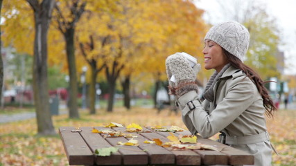 Fall woman sitting in autumn park drinking coffee