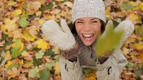 Fall woman excited and happy with autumn leaves