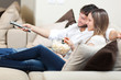 Happy young couple watching television together at home