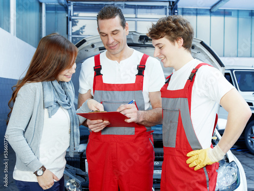 Customer and mechanics in a garage look at a quotation