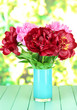 Beautiful peonies in vase on table on bright background