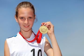 Uśmiechnięta dziewczyna ze złotym medalem.