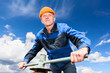 Senior worker in hardhat with pipe valve against blue sky