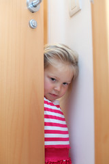 Shy little girl hiding behind the door