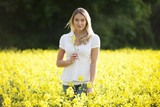 A young woman standing in a rape seed field holding a flower